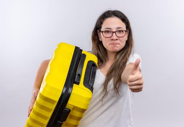 Giovane ragazza in t-shirt bianca che tiene la valigia di viaggio sorridente che mostra i pollici in su