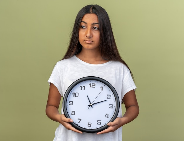 Giovane ragazza in maglietta bianca con orologio da parete che guarda da parte con una faccia seria in piedi su sfondo verde