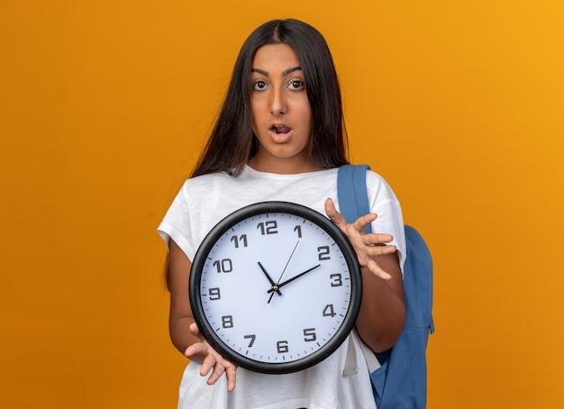 Giovane ragazza in maglietta bianca con orologio da parete che guarda la telecamera stupita e sorpresa in piedi su sfondo arancione
