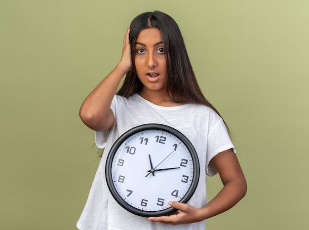 Giovane ragazza in maglietta bianca che tiene l'orologio da parete che guarda la telecamera confusa con la mano sulla testa in piedi sopra il verde