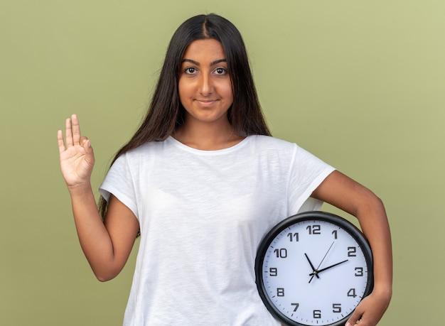 Giovane ragazza in maglietta bianca che tiene l'orologio da parete che guarda l'obbiettivo con il sorriso sul viso facendo segno ok