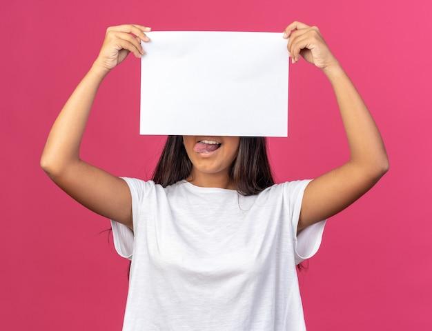 Giovane ragazza in maglietta bianca che tiene un foglio di carta bianco bianco davanti al viso sorridente in piedi sopra il rosa