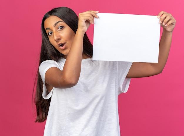 Giovane ragazza in maglietta bianca che tiene un foglio di carta bianco bianco che guarda la telecamera sorpresa e stupita in piedi su sfondo rosa