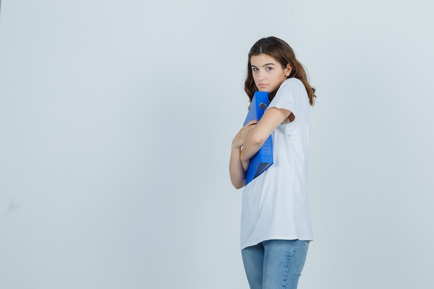 Young girl in white t-shirt hugging folder and looking embarrassed , front view.