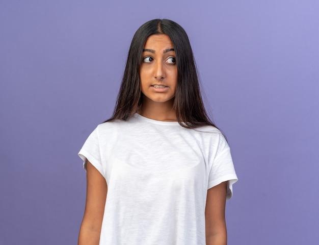 Giovane ragazza in maglietta bianca che guarda da parte confusa e molto ansiosa in piedi su sfondo blu