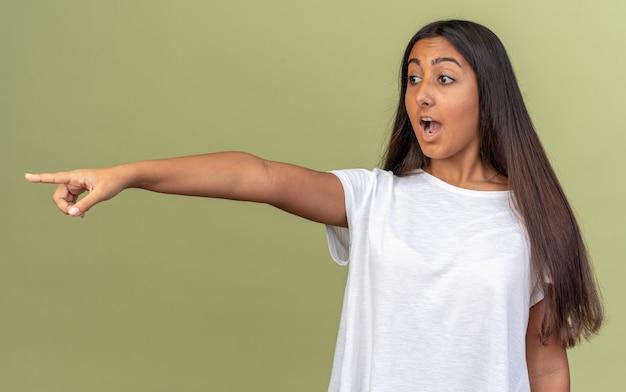 Giovane ragazza in maglietta bianca che guarda da parte indicando con il dito indice qualcosa che è sorpresa e stupita in piedi su sfondo verde