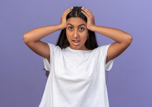 Giovane ragazza in maglietta bianca che guarda la telecamera stupita e sorpresa con le mani sulla testa in piedi su sfondo blu