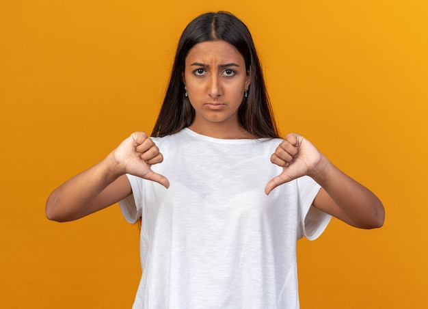 Young girl in white t-shirt looking at camera being displeased showing thumbs down standing over orange