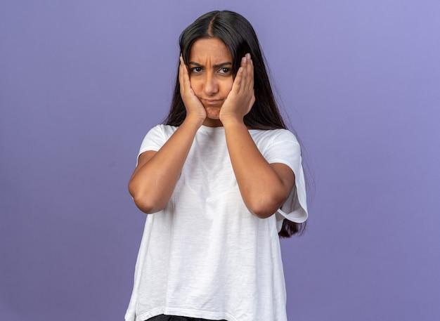 Giovane ragazza in maglietta bianca che guarda la telecamera confusa e molto ansiosa con le mani sul viso in piedi su sfondo blu