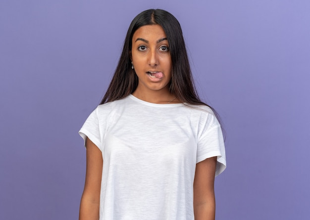 Young girl in white t-shirt looking at camera happy and cheerful sticking out tongue standing over blue background