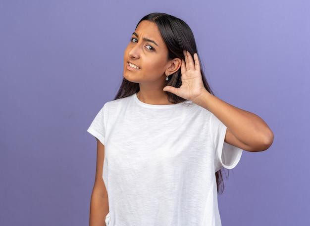 Giovane ragazza in maglietta bianca che guarda l'obbiettivo incuriosito con la mano sull'orecchio cercando di ascoltare qualcosa in piedi su sfondo blu