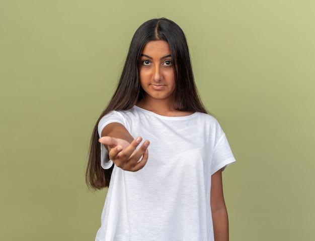 Giovane ragazza con una maglietta bianca che guarda la telecamera facendo un gesto con la mano sorridente amichevole