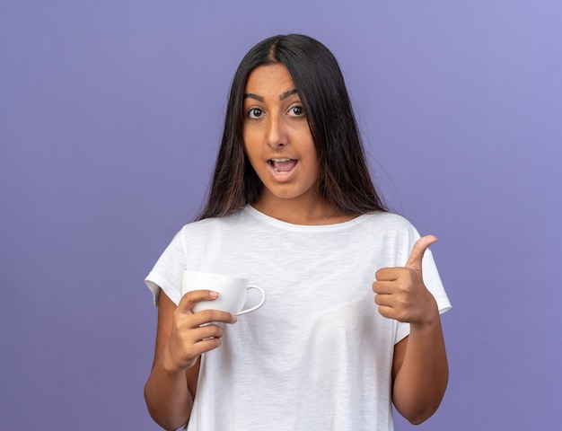 Young girl in white t-shirt looking at camera smiling cheerfully showing thumbs up standing over blue