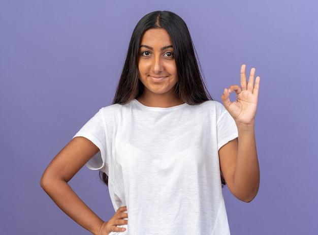 Ragazza in maglietta bianca che guarda l'obbiettivo sorridente fiducioso mostrando segno ok