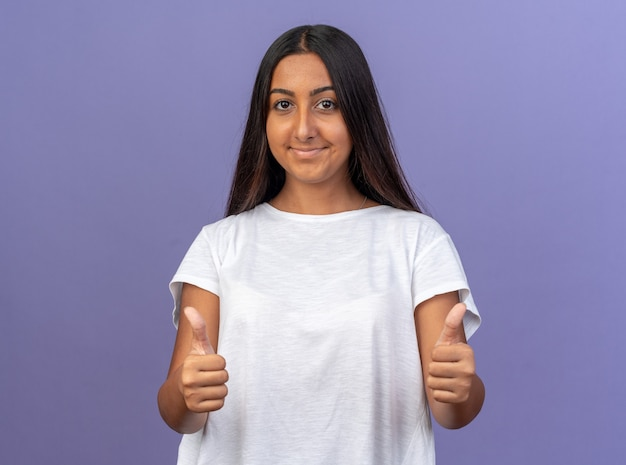 Giovane ragazza in maglietta bianca che guarda l'obbiettivo sorridente fiducioso che mostra i pollici in su