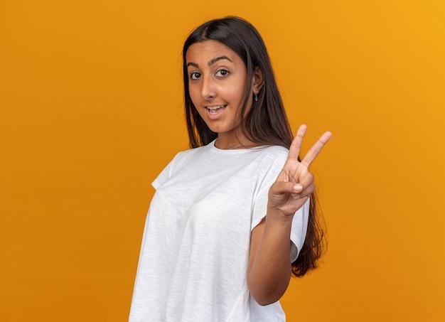 Ragazza in maglietta bianca che guarda l'obbiettivo sorridente fiducioso che mostra il v-sign in piedi sull'arancia