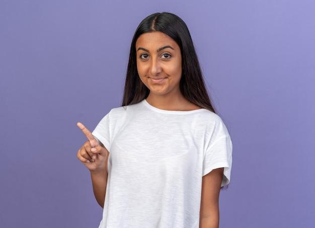 Giovane ragazza in maglietta bianca che guarda la telecamera sorridente che punta con il dito indice a lato in piedi su sfondo blu