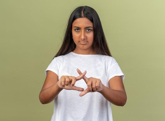 Giovane ragazza in maglietta bianca che guarda la telecamera con il viso serio che incrocia gli indici che fanno un gesto di arresto in piedi sul verde