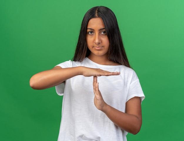 Giovane ragazza in maglietta bianca che guarda la telecamera con una faccia seria che fa un gesto di pausa con le mani