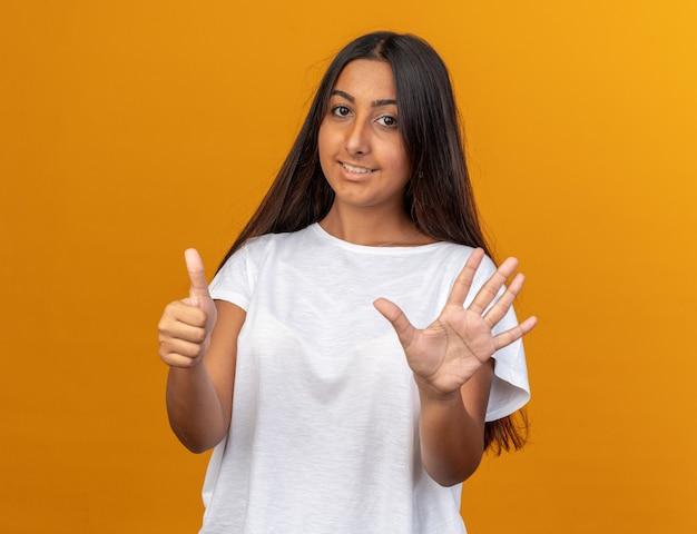 Giovane ragazza in maglietta bianca che guarda la telecamera con un sorriso sul viso che mostra e punta verso l'alto con le dita numero sei