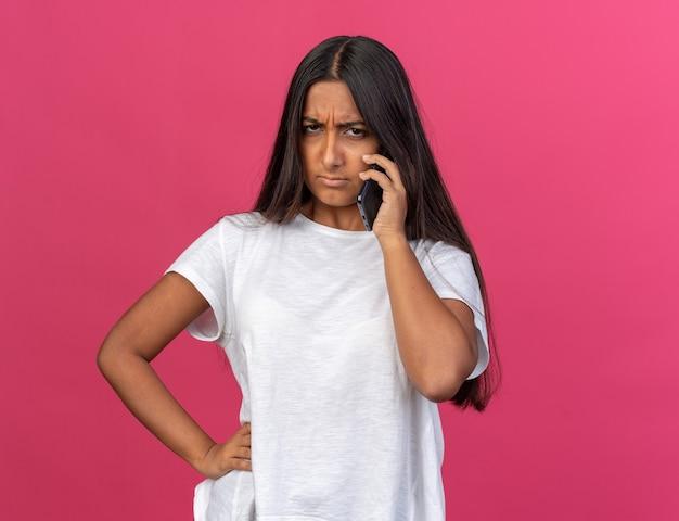 Giovane ragazza in maglietta bianca che sembra accigliata dispiaciuta mentre parla al telefono cellulare in piedi sopra il rosa