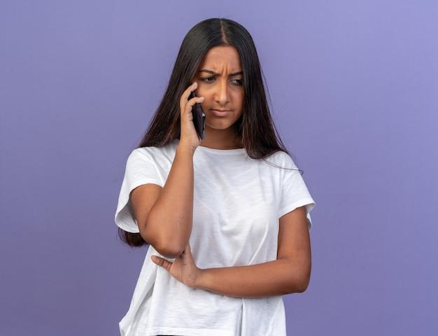 Giovane ragazza in maglietta bianca che sembra dispiaciuta mentre parla al cellulare in piedi sopra il blu