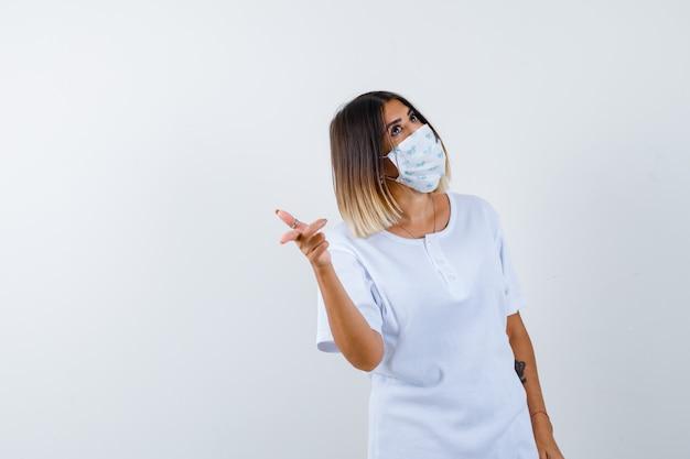 Giovane ragazza in maglietta bianca e maschera che punta alla telecamera con il dito indice e guardando pensieroso, vista frontale.