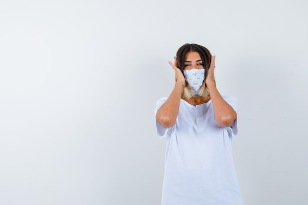Young girl in white t-shirt and mask pressing hands on ears and looking serious , front view.