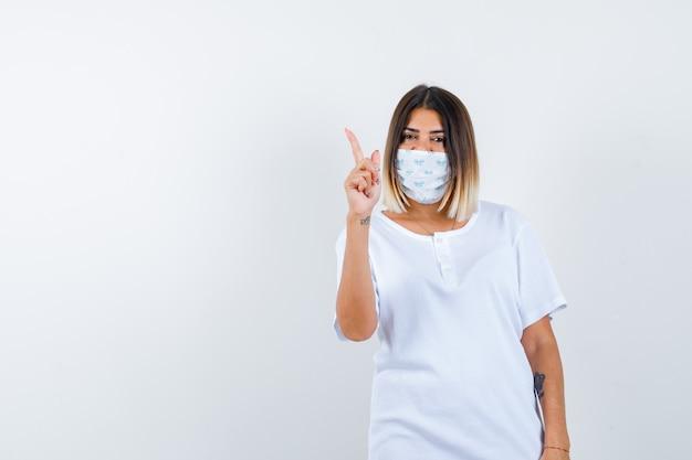 Giovane ragazza in maglietta bianca e maschera alzando il dito indice nel gesto di eureka e guardando sensibile, vista frontale.
