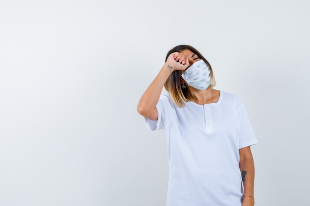 Young girl in white t-shirt and mask rubbing eye with fist and looking tired , front view.