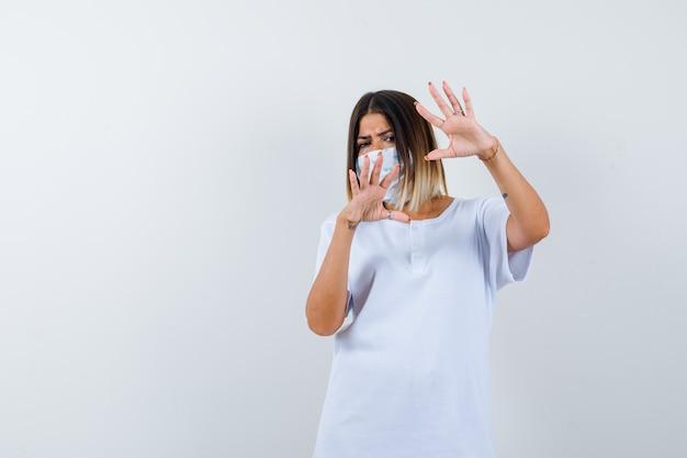 Giovane ragazza in maglietta bianca, maschera che mostra il gesto di restrizione e che sembra seria, vista frontale.