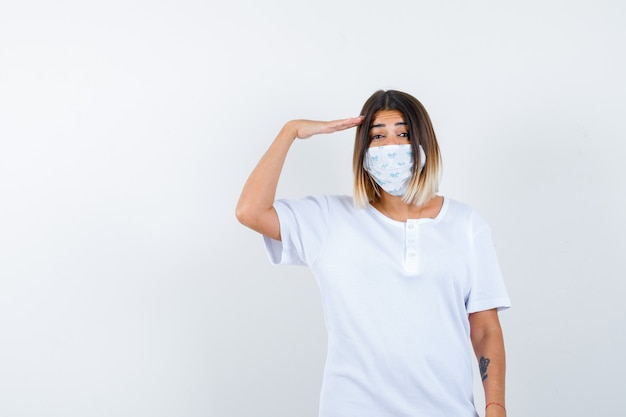 Young girl in white t-shirt and mask showing salute gesture and looking confident , front view.