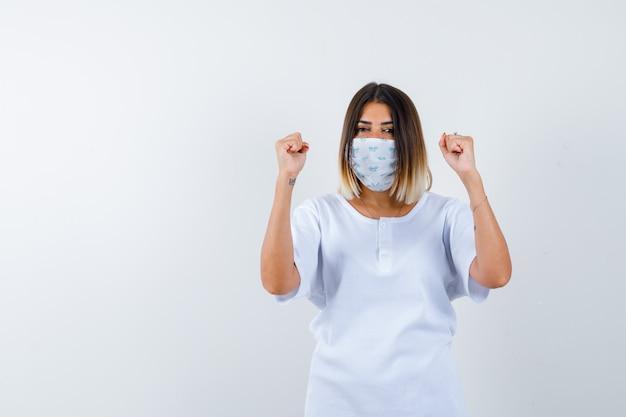 Giovane ragazza in maglietta bianca e maschera che mostra il gesto del vincitore e sembra fortunato, vista frontale.