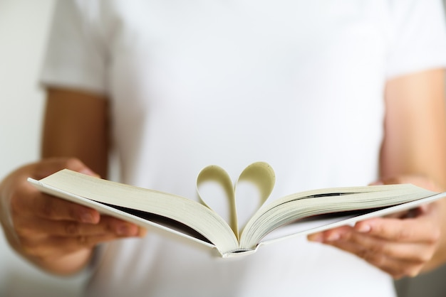 Young girl in white t-shirt reading opened book with shape of heart, love concept.