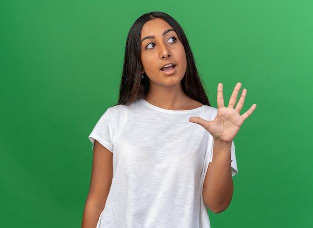 Ragazza in maglietta bianca che mostra il numero cinque che guarda da parte perplessa
