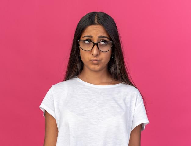 Giovane ragazza in maglietta bianca con gli occhiali che guarda da parte con un'espressione triste che increspa le labbra in piedi sul rosa