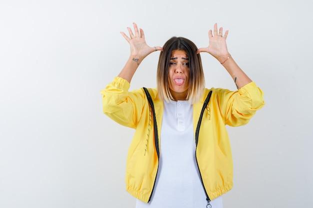 Giovane ragazza in maglietta bianca, giacca gialla che tiene le mani vicino alla testa, con la lingua fuori e guardando divertito, vista frontale.