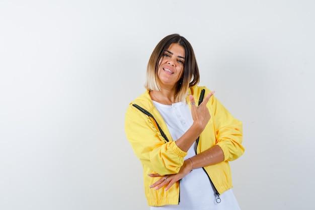 Giovane ragazza in maglietta bianca, giacca gialla che punta a destra con il dito indice e sembra allegra, vista frontale.