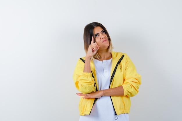 Giovane ragazza in maglietta bianca, giacca gialla che alza il dito indice nel gesto di eureka e sembra sensibile, vista frontale.