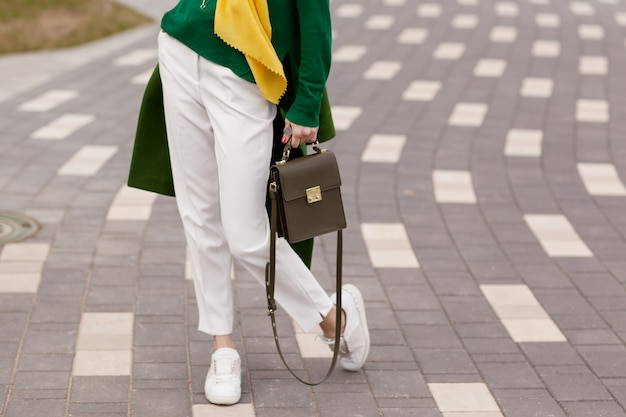 A young girl in white trousers, warm greens coat.