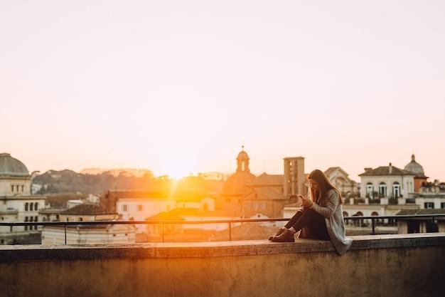 日没時に屋上で携帯電話を使う少女。