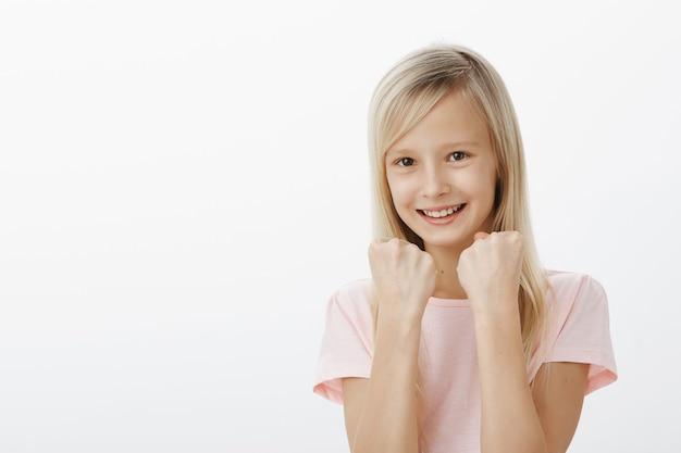若い女の子は皆に彼女の強みを見せます。ピンクのtシャツを着た陽気な愛らしい娘、握りこぶしを上げ、ボクシングポーズで立って、浮気し、広く笑って、防御