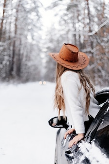 A young girl in a winter forest among the road in the car looks into the distance