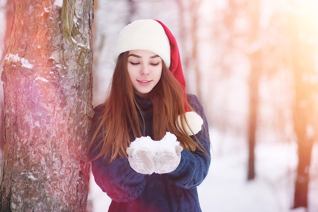 A young girl in a winter park on a walk. christmas holidays in the winter forest. girl enjoys winter in the park.