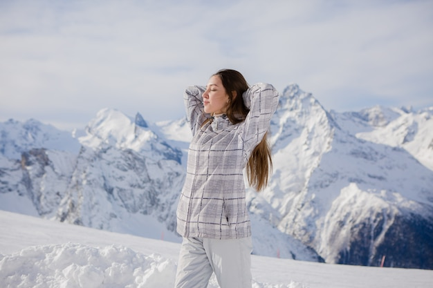 Young girl in a winter suit looking at the mountains
