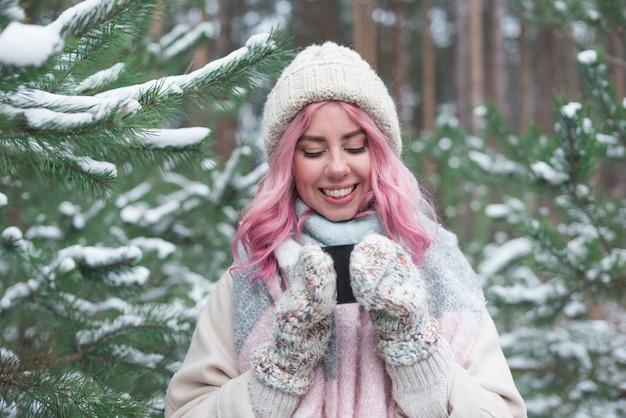 Молодая девушка с розовыми волосами пьет чай в зимнем лесу