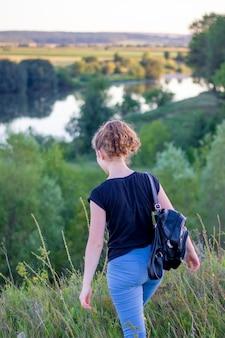 自然の中を歩きながらバックパックを持つ少女。自然の中のアクティブな休息