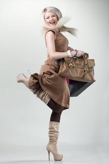 手にバッグとパッケージを持つ少女