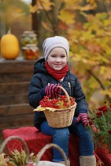秋の公園でガマズミ属の木のバスケットを持つ少女