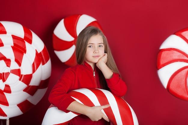 大きなクリスマスキャンディケインを持つ少女